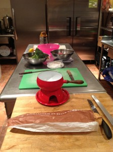 The line-up: French bread, fondue pot, chopping boards, broccoli, apples and two kinds of cheeses!